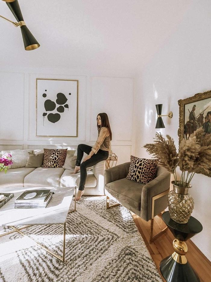 plante plumeau tapis fausse fourrure blanc et noir motifs géométriques table marbre salon blanc cadre peinture doré