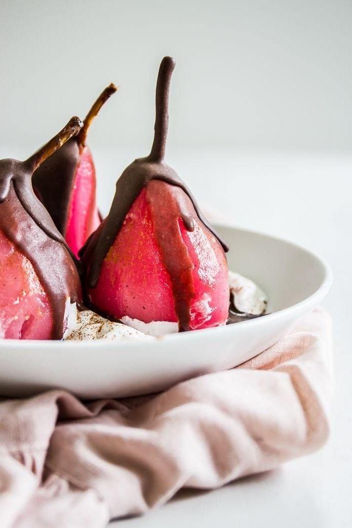 poires pochées au vin rouge enveloppées de chocolat avec de la creme fraiche dans assiette blanche