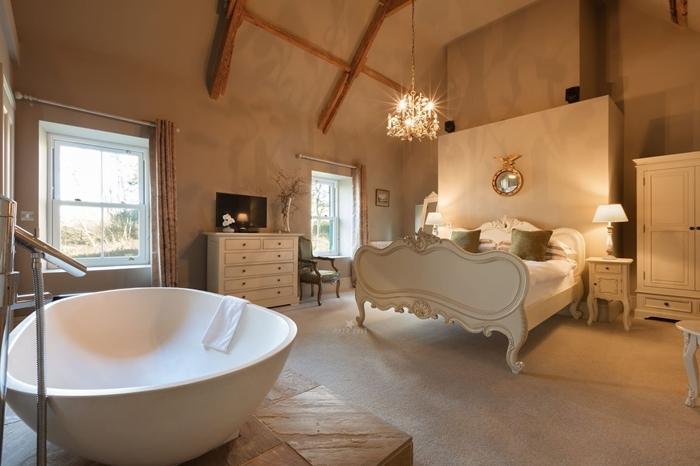 poutres bois apparentes baignoire dans chambre autoportante revêtement sol bois commode blanche miroir cadre or lampe de chevet