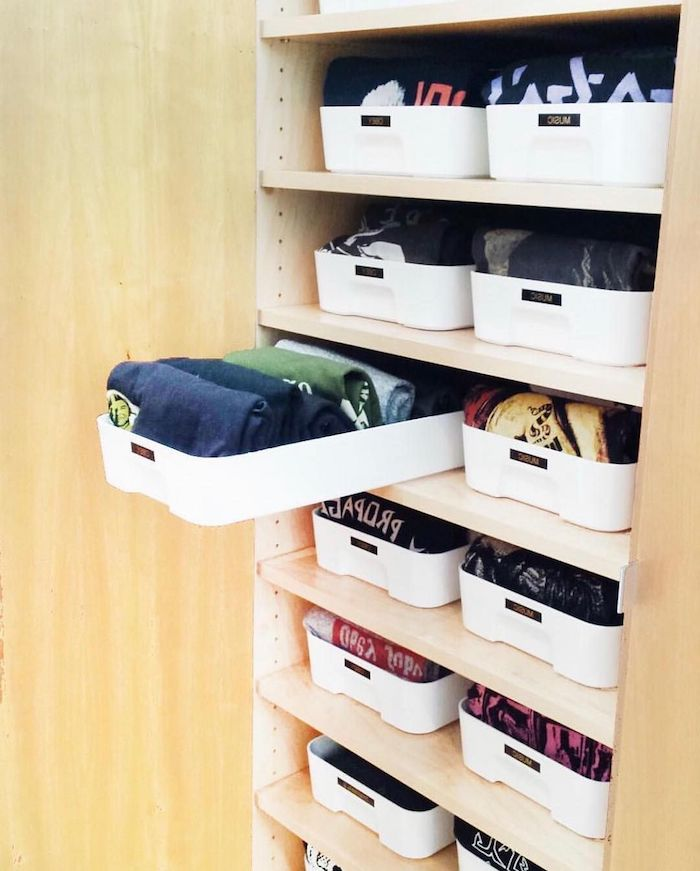 rangement sous vetement dans un armoire avec des boites des pulls et des blouses dans un tiroir