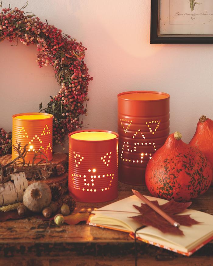 recylage boite de conserve avec motifs jakc o lantern réalisés à trous avec des lumières bougies à l intérieur bougie halloween decoration a faire soi meme