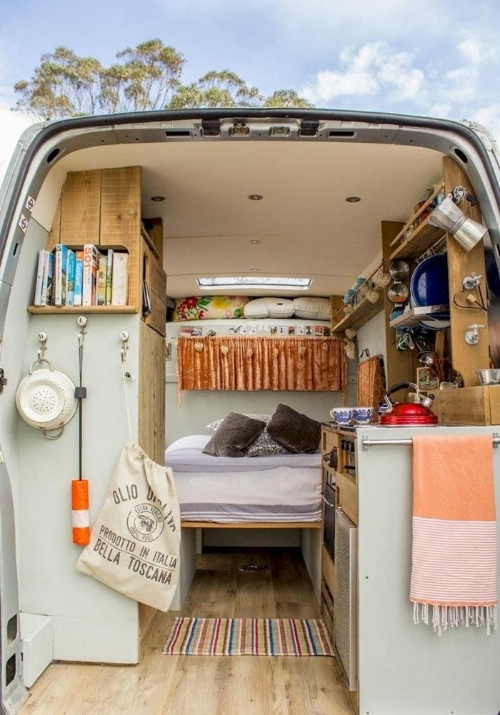 renault trafic aménagé lit et petite cuisine meubles bois rangement mural étagère bois tapis multicolore coussin gris foncé