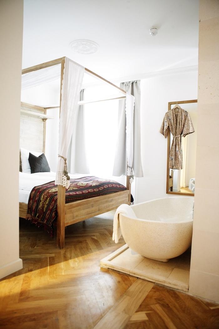 revêtement de sol parquet bois clair baignoire dans chambre autoportante cadre de lit bois baldaquin couverture de lit motifs ethniques