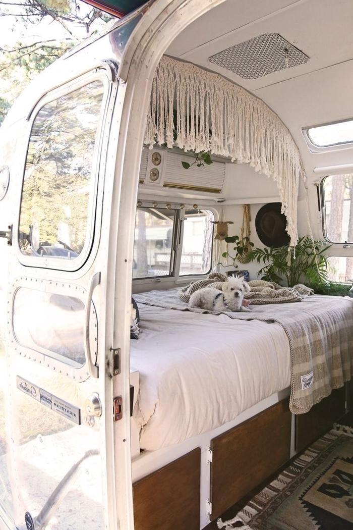 rideau macramé petit fourgon aménagé avec lit bois parquet foncé tapis gris motifs rayures jeté lit beige et gris plantes