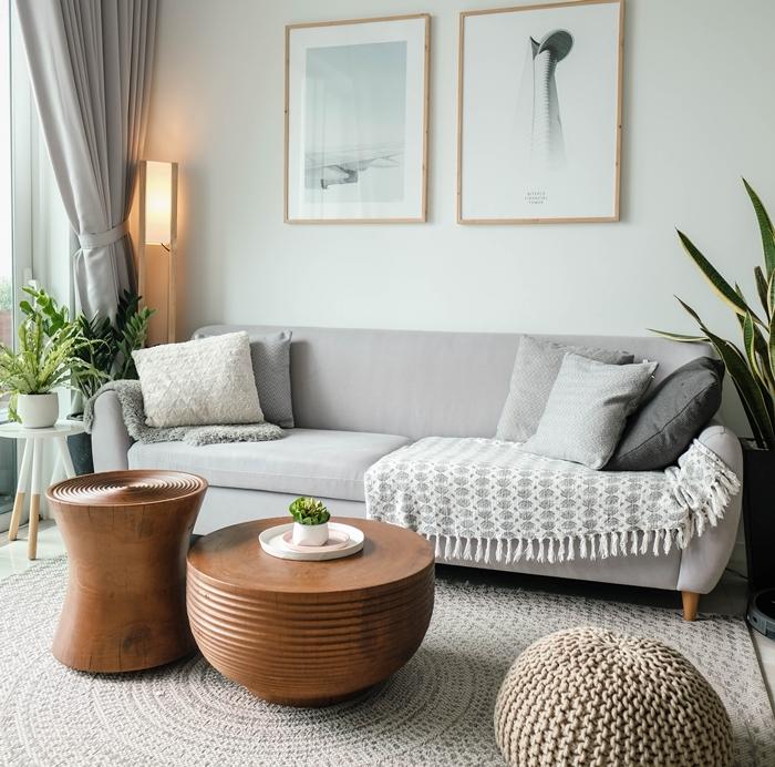 rideaux gris clair lampe à poser bois table basse ronde bois tapis rond beige canapé gris plaid à franges pouf crochet ottoman cadre photo bois
