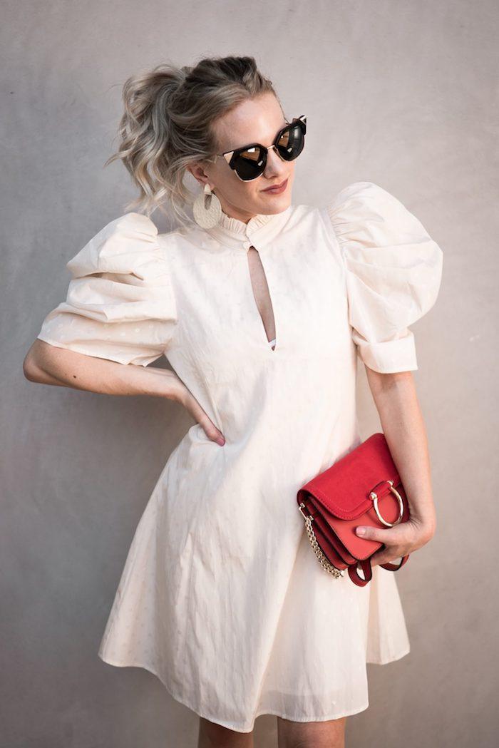 robe manche ballon en blanc portee avec un sac a main rouge boucles d oreilles et lunettes