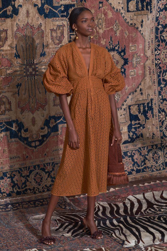 robe manche bouffante en ochre un model devant tapis sur la mur deffile de mode