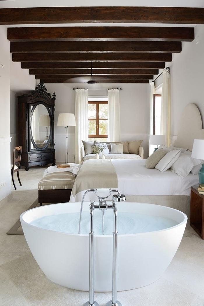 salle d eau dans chambre baignoire autoportante plafond blanc poutres bois foncé apparentes meuble bois foncé miroir ovale