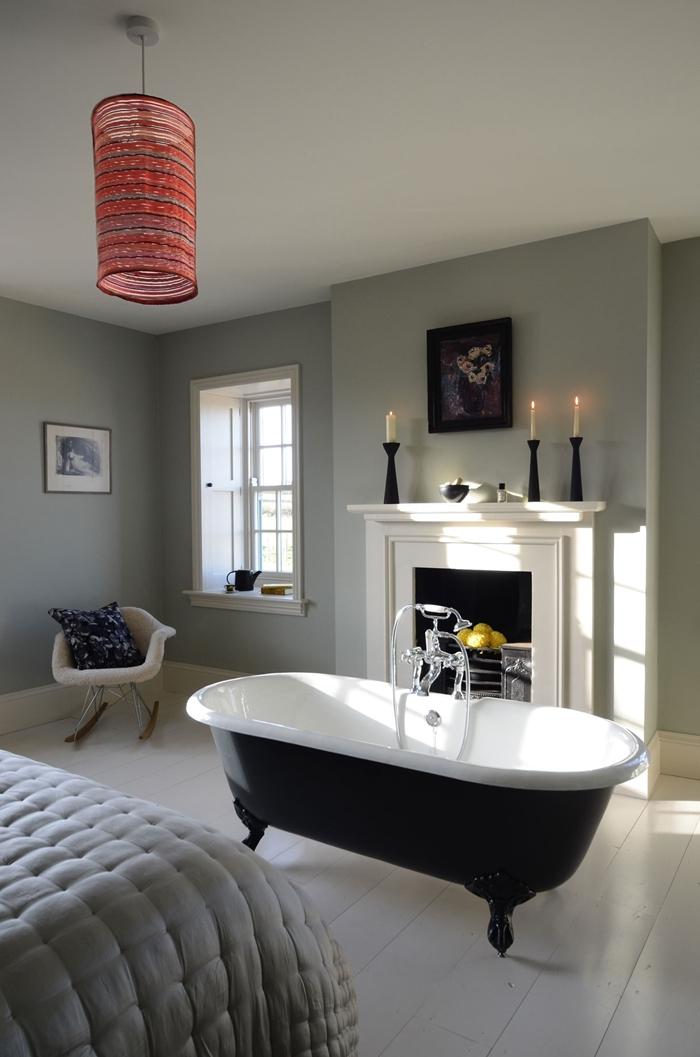 salle de bain dans chambre avec cheminée décorative peinture murale chambre adulte gris clair plafond blanc chaise relax