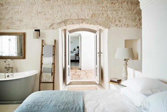 salle de bain dans chambre style campagne revêtement mur briques lampe de chevet blanche baignoire autoportante échelle serviette bain