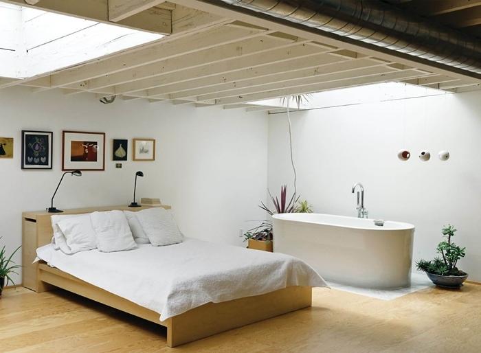 salle de bain ouverte sur chambre revêtement de sol parquet bois lit bois plantes vertes intérieur mur cadres bois