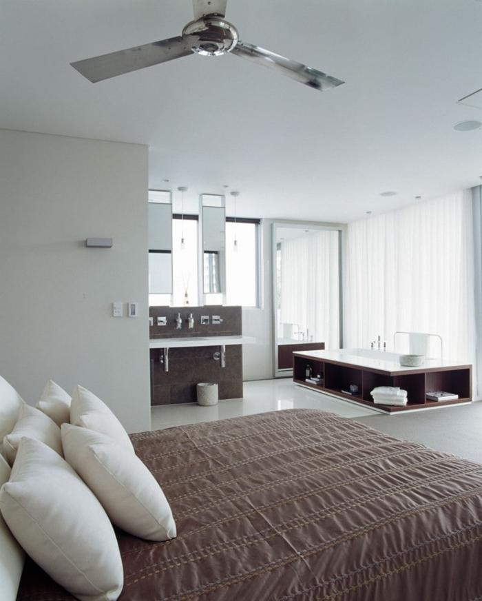salle de bain ouverte sur chambre ventilateur de plafond meubles rangement ouvert serviettes de bain rideaux blancs