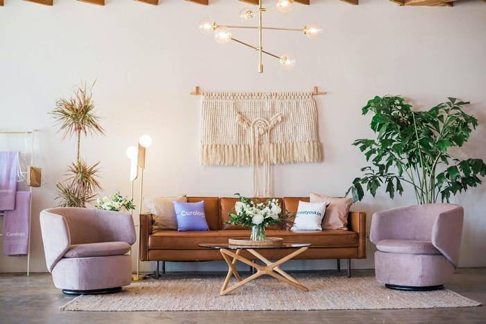 salon cocooning fauteuil en velours rose pastel canape cuir marron suspension macrame poutres apparentes plafond bois