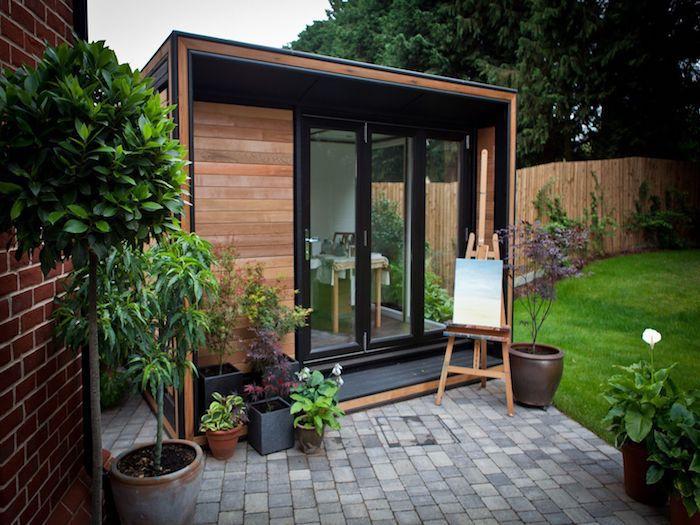 studio de jardin 20m2 un chevalet pose pres de bureau et quelaues pots a fleurs