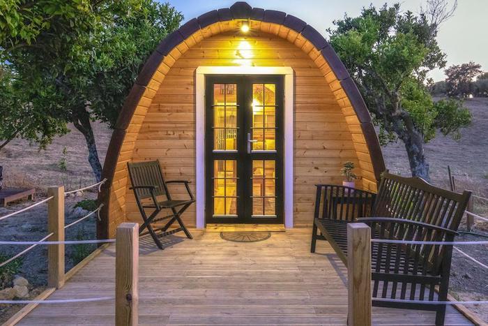 studio de jardin en forme irreguliere avec un banc et une chiase en bois devant sur un plateforme