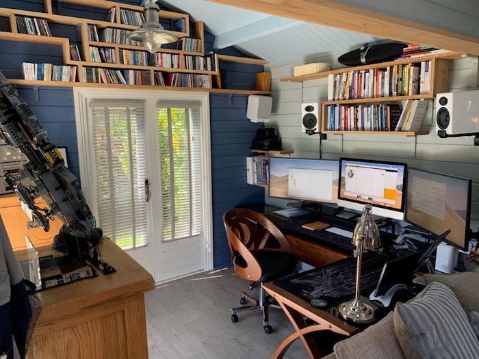 studio de jardin en style rondin des livres sur les etageres des ordinateurs sur le bureau er murs bleues