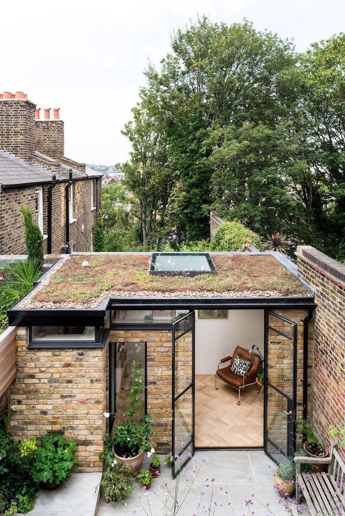 studio de jardin habitable en pierre avec un toit plat et cadres noirs en style moderne