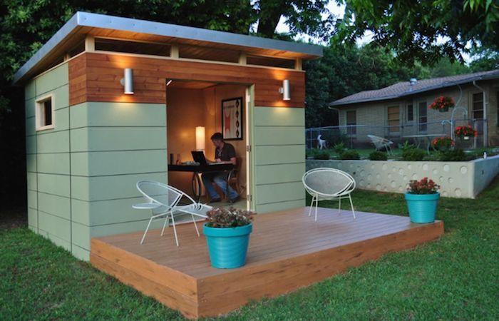 studio de jardin habitable en vert reseda pres de la maison avec deux chaises et deux fleurs un homme travaille sur ordinateur