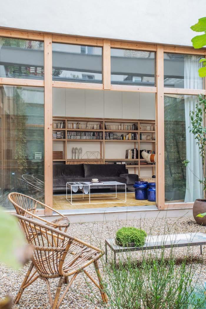 studio de jardin habitable precede de gravier avec grandes fenetres et une biblioteque deux chiases ratin