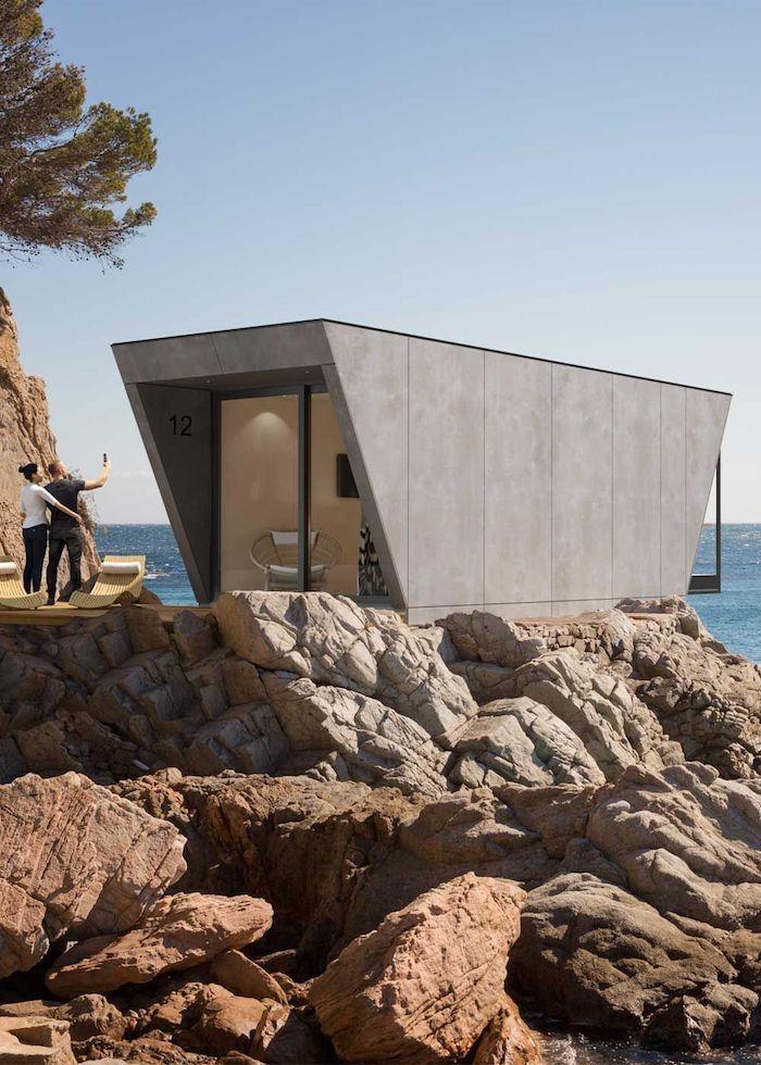 studio de jardin perche sur un rocher au bord de la mer donant sur la plage design moderne