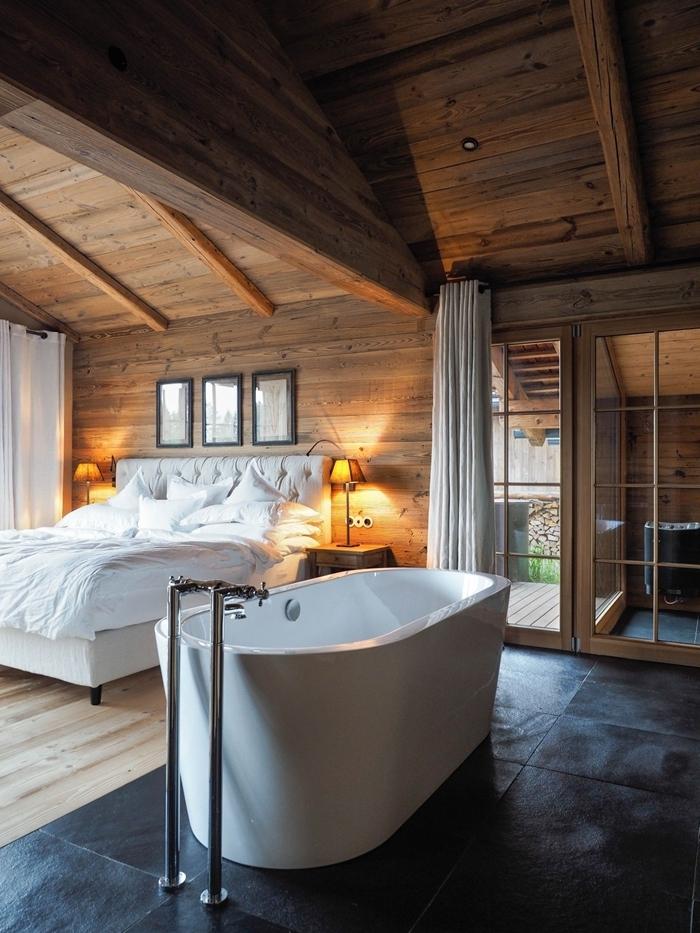suite parentale salle de bain déco chalet chambre rustique revêtement de plafond poutres apparentes bois baignoire blanche autoportante