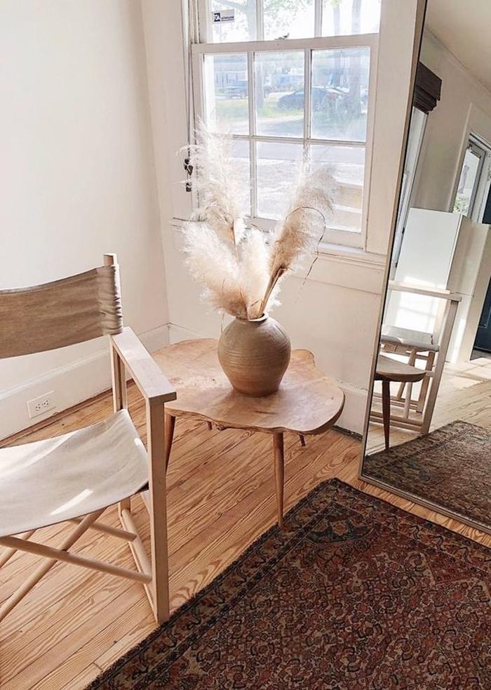 tapis motifs ethniques marron chaise bois tissu déco avec herbe de la pampa parquet bois clair table basse bois clair