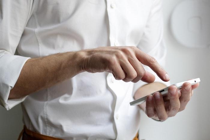 telephone portable mac blanc chemise blanche homme qui vient de telephonner qqn