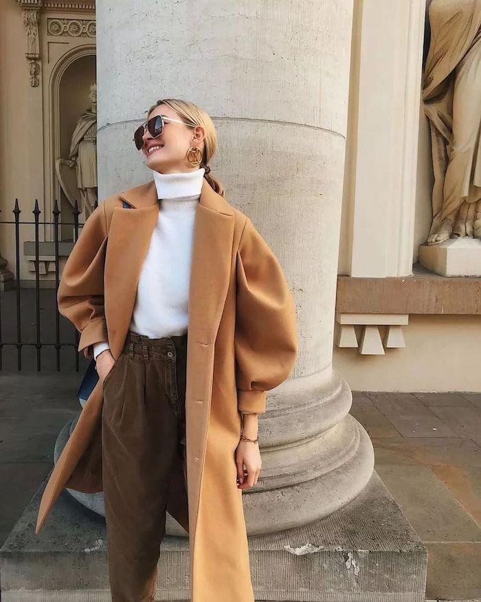 tendance automne hiver 2020 femme avec manteau beige et pull a col roule devant une colonne