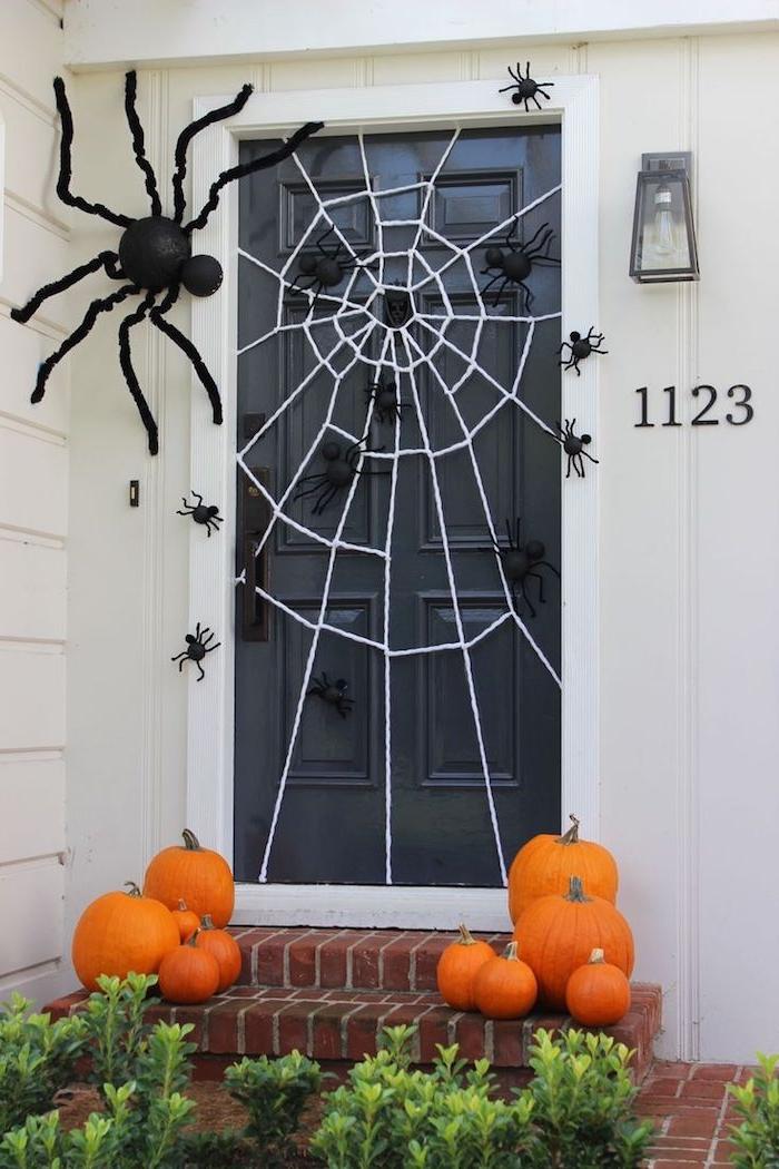 toile d araingée en fils blancs araignées artificielles et courges halloween de taille differente, déco halloween extérieurе à faire soi-même