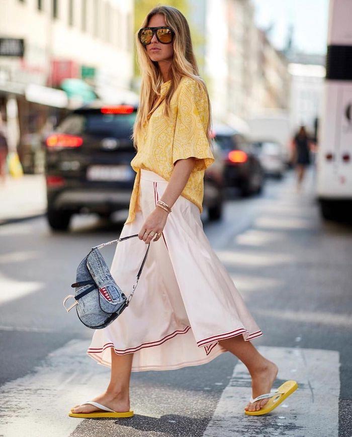 une jeune femme dans la rue sac en denim jupe longue et blouse jaune asymetrique avec des tongues style annee 2000