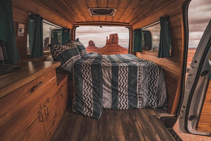 véhicule aménagé revêtement intérieur van isolation matériaux mur bois parquet plafond petite cuisine lit rideaux verts