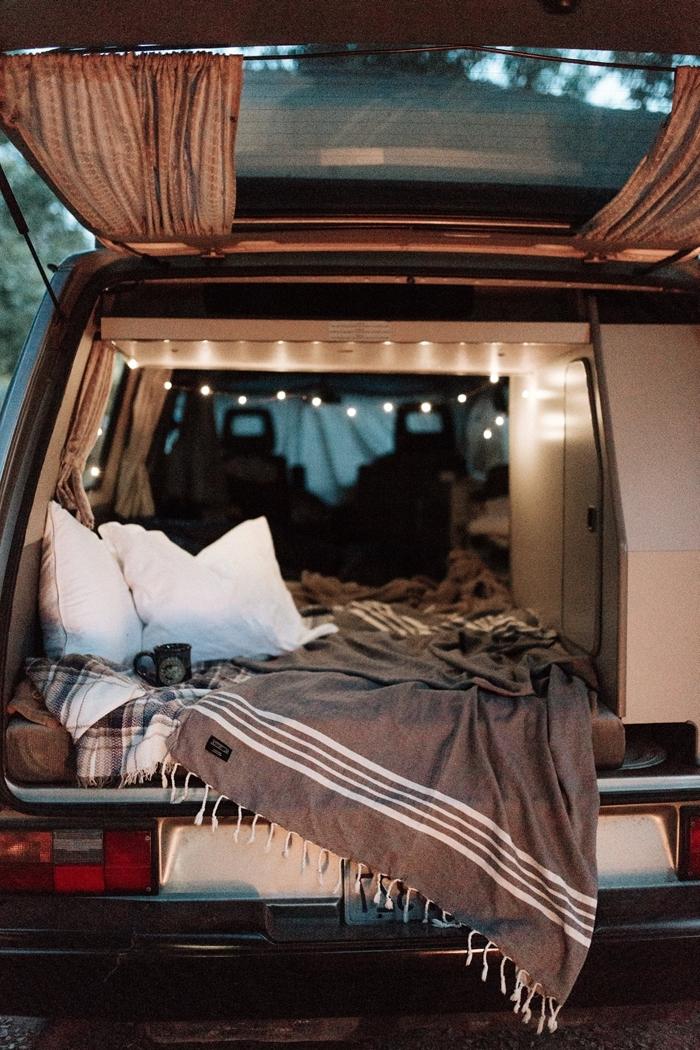 van aménagé avec lit coussins décoratifs guirlande lumineuse tasse thé jeté lit frange décoration véhicule bohème