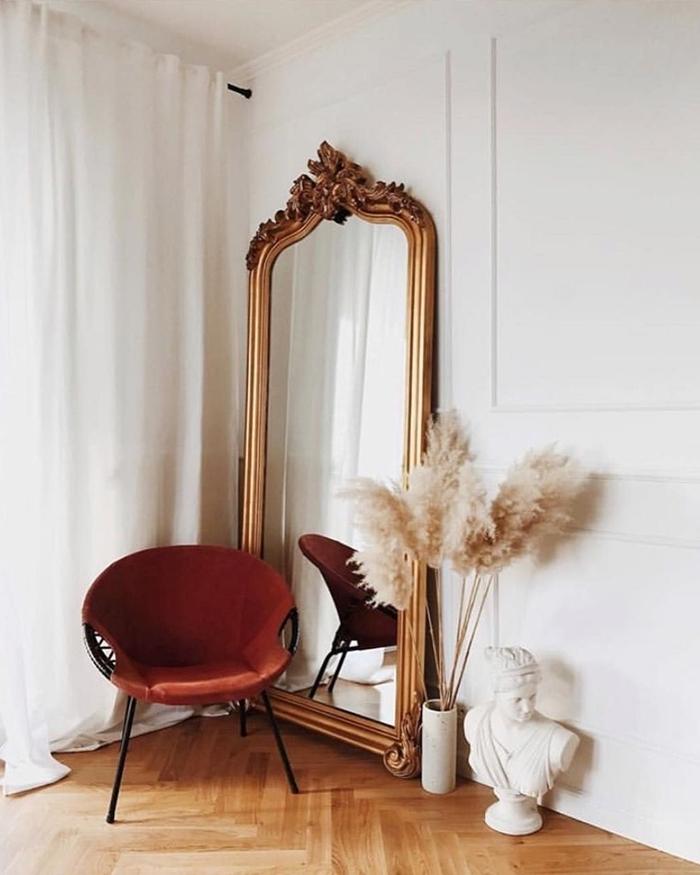 vase pampa design intérieur déco appartement parisien statuette parquet bois rideaux longs chaise noire miroir doré
