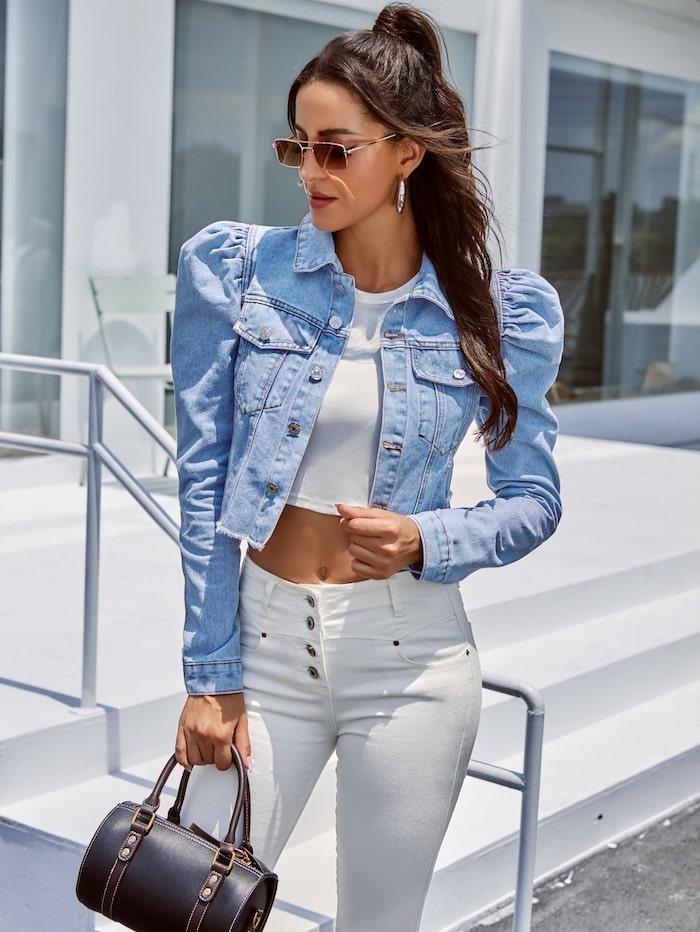 veste en denim aux manches bouffantes avec un pantalon blanc skinny a taille haute et un top court une femme devant escalier