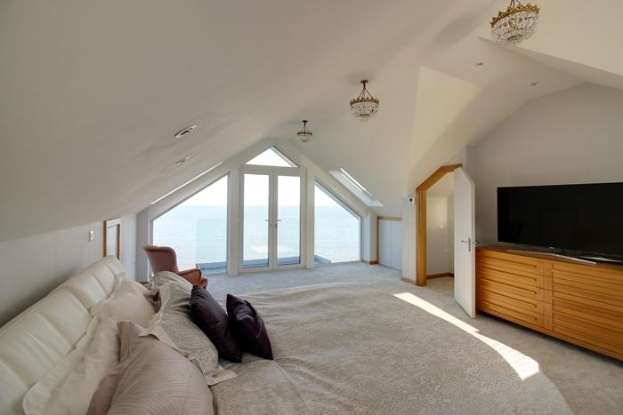 aménagement chambre sous comble design épuré lustre cristaux tête de lit cuir blanc fenêtre balcon commode bois