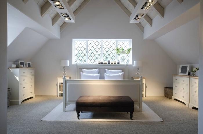 aménagement sous comble chambre adultes murs blancs plafond poutres bois blanc cadre de lit banquette velours