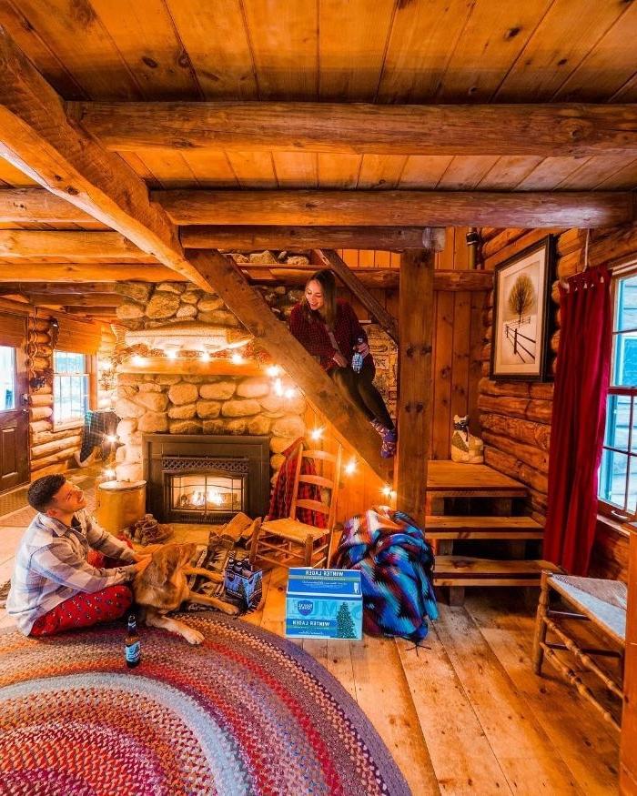 ambiance cocooning dans chalet moderne avec cheminée de pierre poutres apparentes murs de bois plaid cocooning