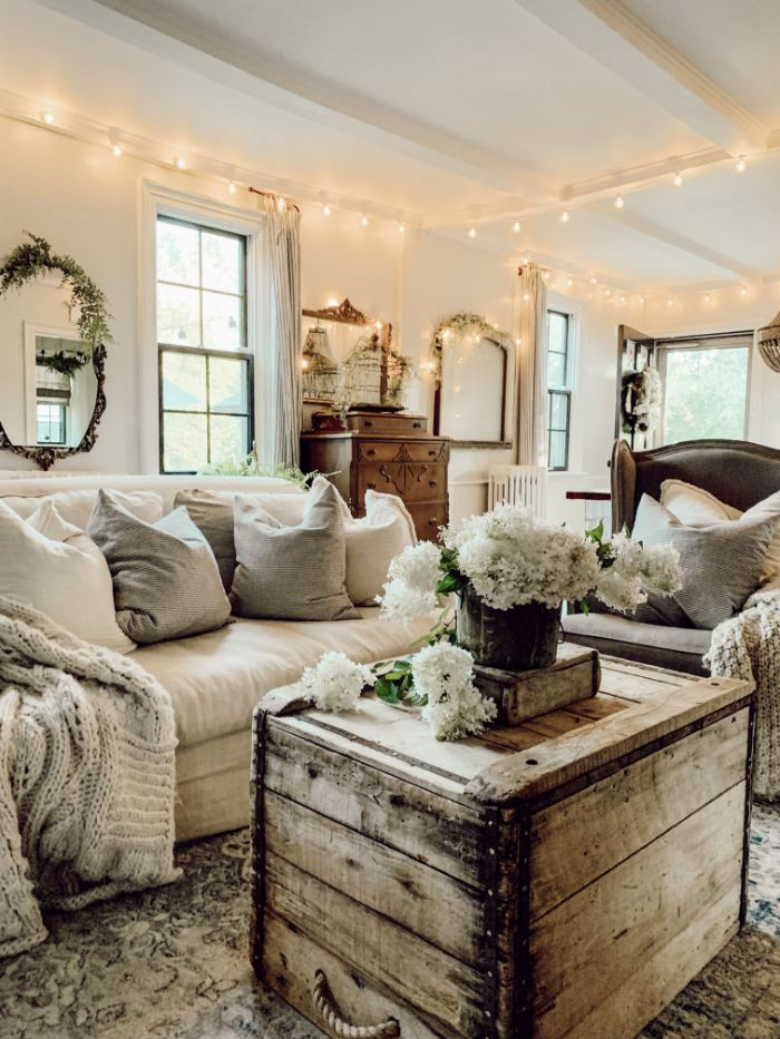 ambiance deco campagne ferme avec table coffre de bois canapé gris clair fauteuil gris deco guirlande lumineuse mobilier vintage tapis usé