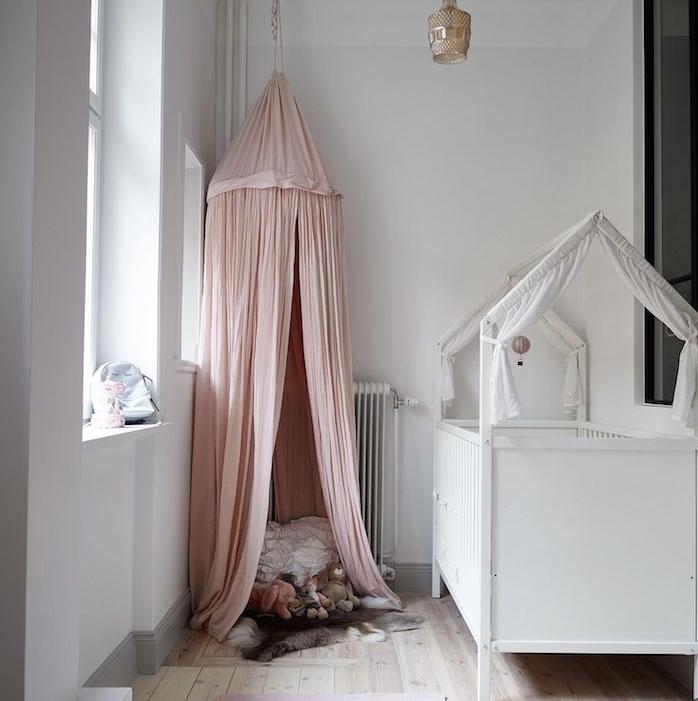aménagement chambre bébé en longueur ambiance déco ccooning avec ciel de lit cabane à voiles roses lit berceau blanc tapis coloré sur parquet bois clair