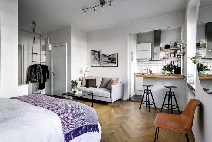 amenagement petit espace parquet bois décoration lit cocooning jeté franges violet éclairage rail industriel canapé velours