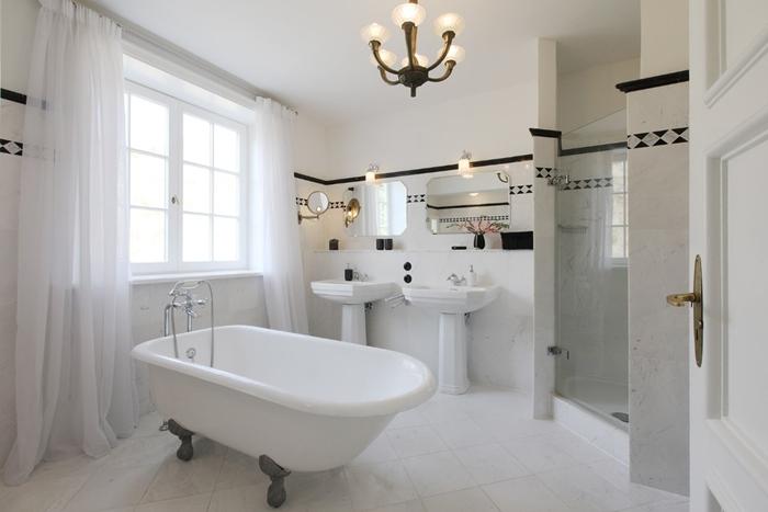 baignoire sur pied salle de bain style ancien double lavabo évier sur piédestal miroir rideaux longs blancs carrelage blanc