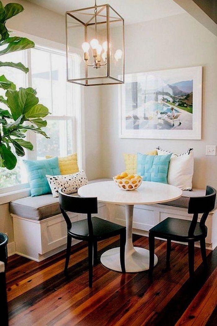 banquette salle a manger avec un sol en pailles deux chaises noirs et une plante verte