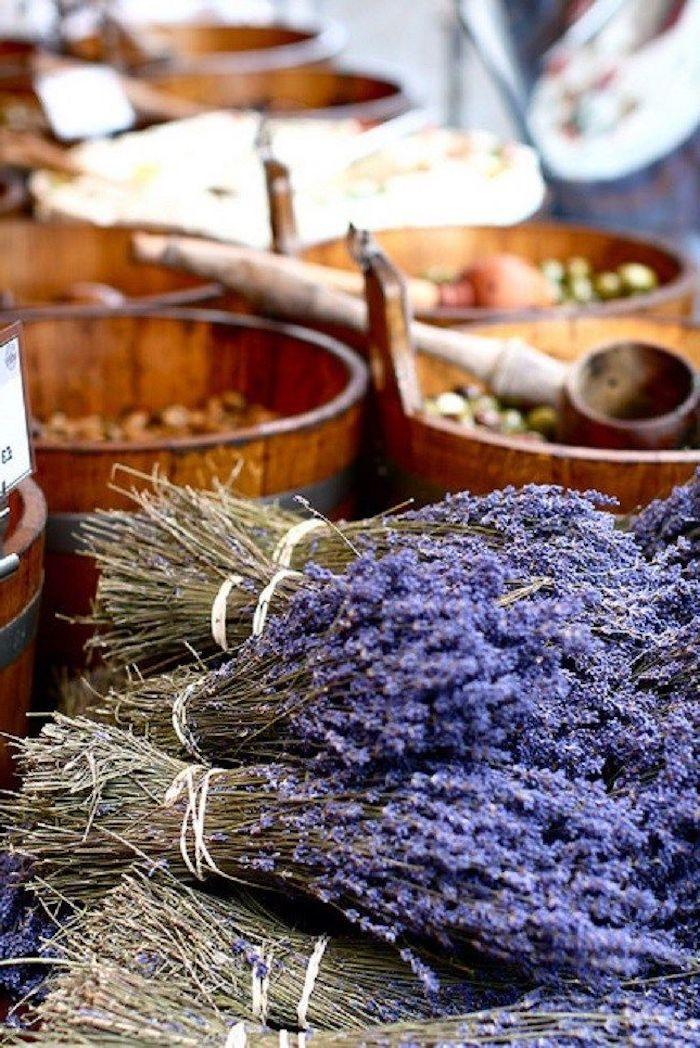 birn de lavande poses sur une table avec des tonnneau en bois pleins d olives