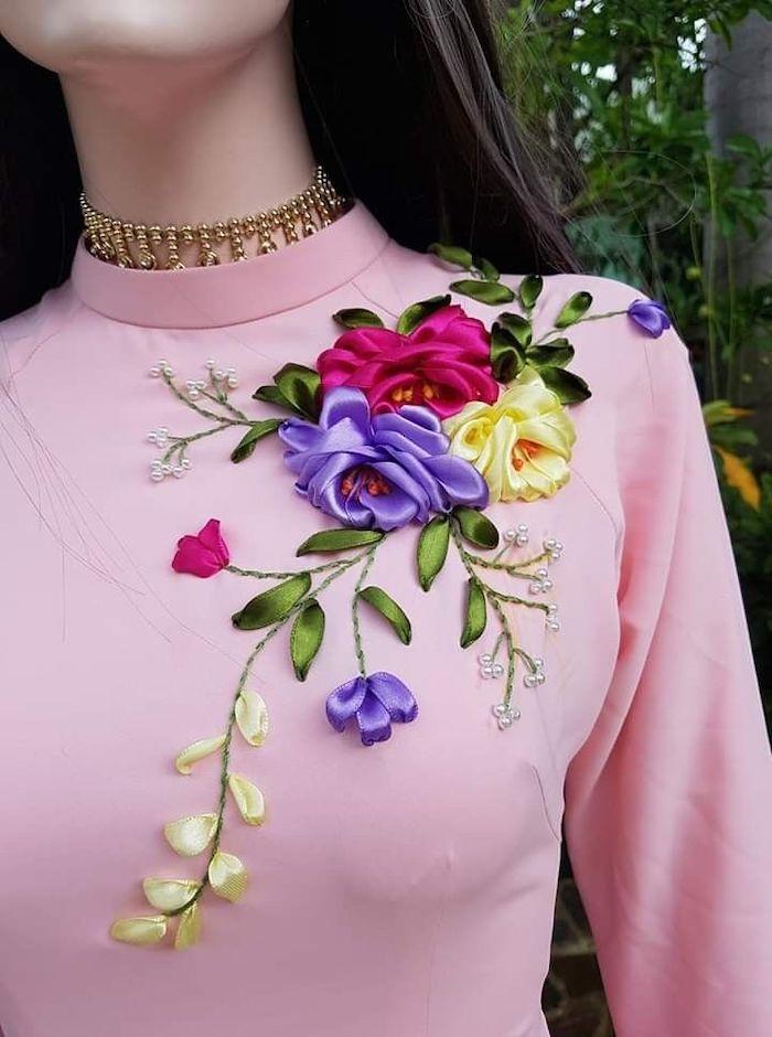 broderie pesonnalisee une femme avec un colier et blouse rose customise avec des rubans