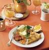 brunch healthy avec0des oeufs et des tartines beurres servi avec jus et de cafe sur une nappe orange