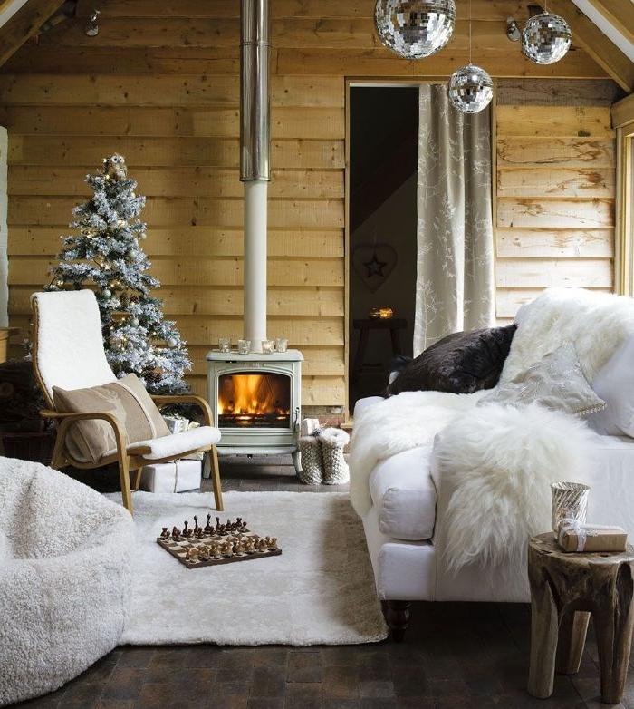 canapé blanc tapis et fauteuil blancs chaise bois cheminée rustique mur de bois et sapin de noel décoré deco chic rustique
