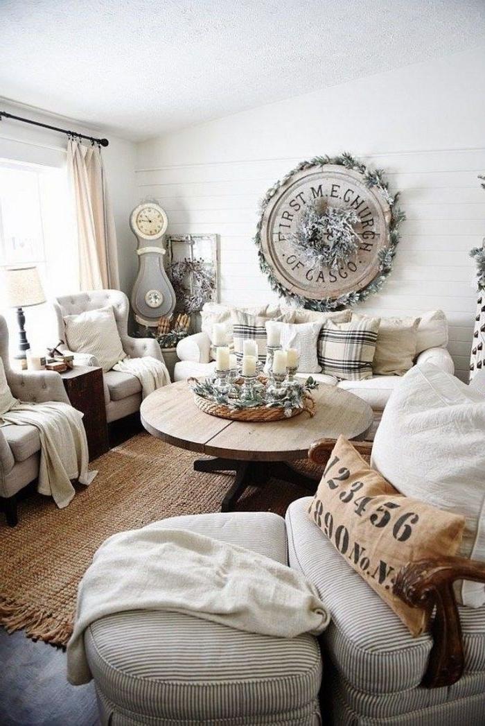 canapé et fauteuils gris et blanc tapis brut murs lambris blanc table bois brut centre de table bougies et branches de pin deco murale rondin