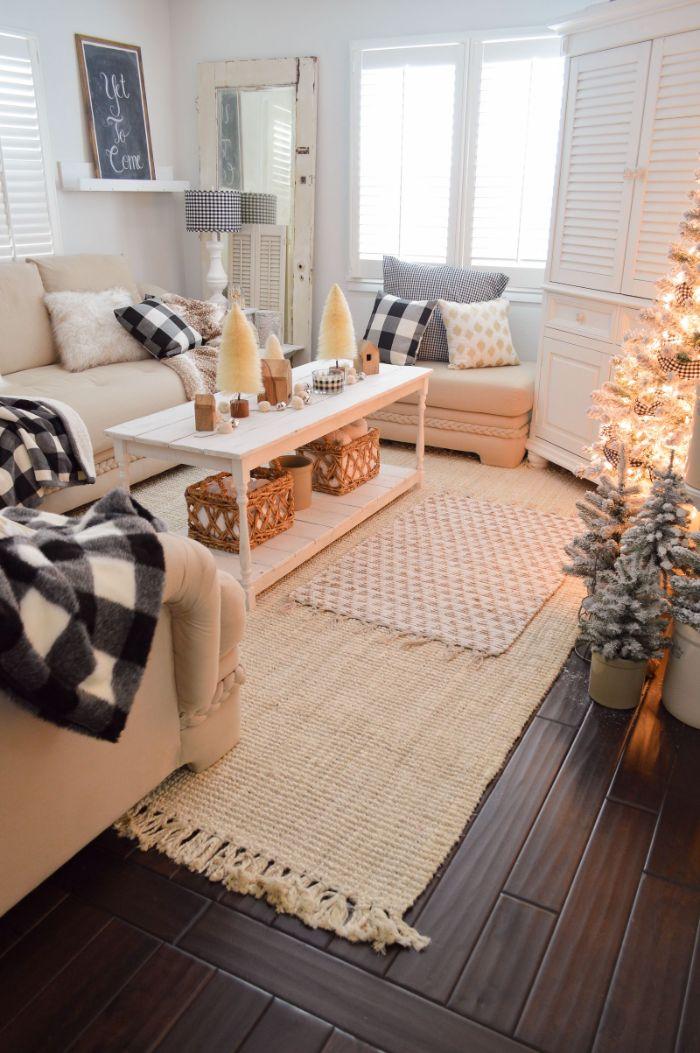 canapés blanc cassé tapis à franges table basse blanche decoration de sapins de tailles variées coussins decoratifs