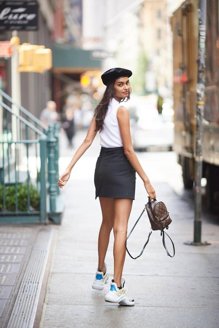 casual chic femme jupe courte noire taille haute t shirt blanc sans manches baskets blanches femme sac à dos cuir marron