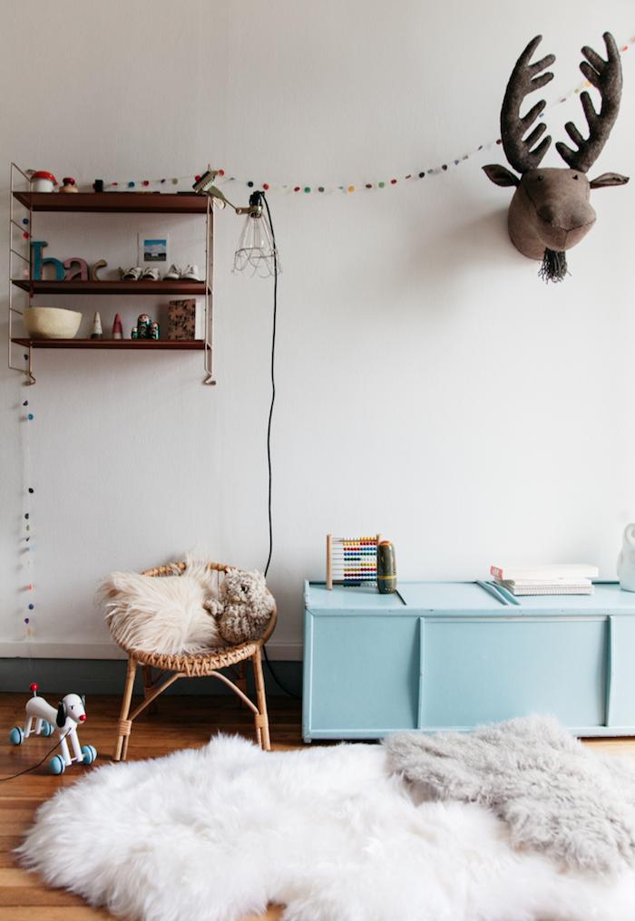 chaise en rotin meuble bas bleu nuit parquet couvert tapis fausse fourrure étagère bois brut murs blancs